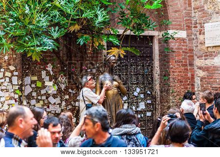 VERONA ITALY - APRIL 16 2016: Tourist kisses the Juliet's statue on April 16 2016 in Verona Italy.