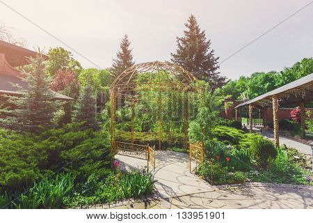 Beautiful landscape design, garden path to metal gazebo and evergreen trees in sunlight. Modern landscaping: Fir trees and blue spruces. Summer garden or park design.