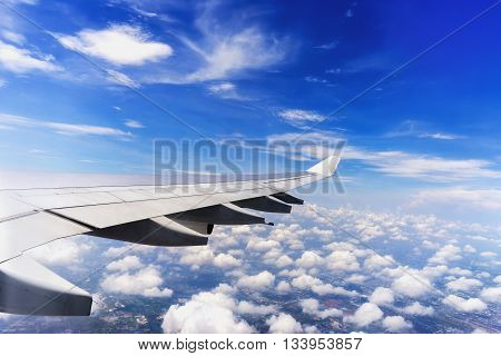 Aircraft wing during flight with blue sky and white clouds looking from aircraft window