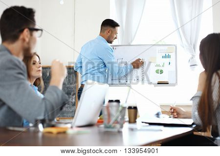 Take a look at our results Handsome young man in glasses standing near whiteboard and pointing on the chart while his coworkers listening and sitting at the table.