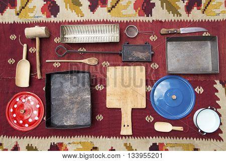 Vintage kitchen utensills on an old shabby carpet