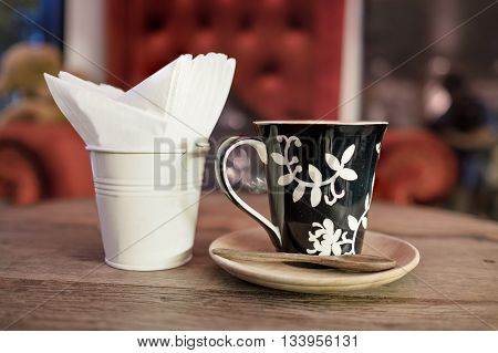 hot coffee with tissue paper coffee on wooden table coffee coffee near red sofa
