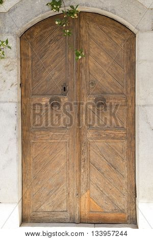 An old wooden door on a marble facade