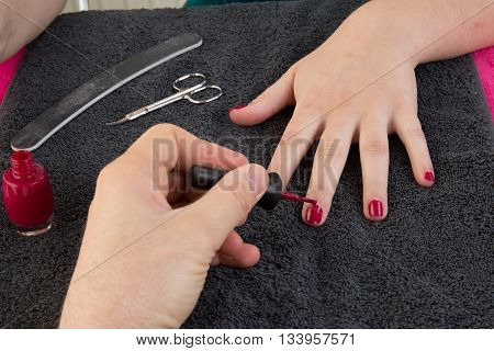 Female Hands Putting A Varnish On Nails Of A Girl