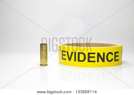 evidence tape with brass bullet case on white background