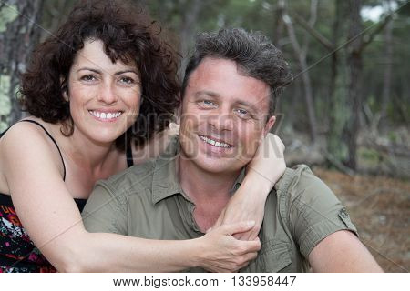 Cheerful Couple Enjoying Togetherness, Sitting In The Forest, Holding Tenderly