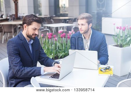 Handsome young businessmen are using laptops for work. They are sitting at table in restaurant. Man is typing and smiling