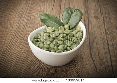 White bowl with green coffee beans on the wood