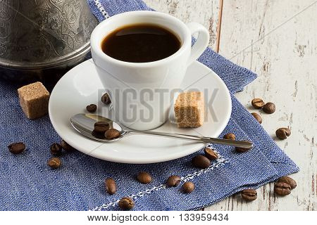 A cup of coffee, spoon, sugar and coffee beans on a napkin on a light wooden background.
