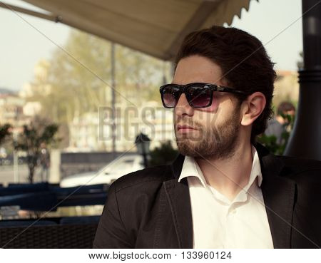 Young bearded man is sitting in outdoor caffe
