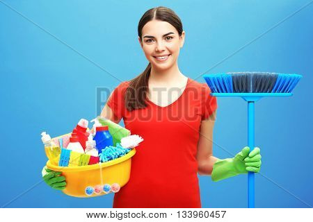 Female cleaner on blue background