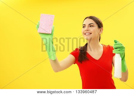 Female cleaner on yellow background