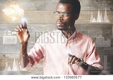 Attractive African Businessman Wearing Glasses Navigating Futuristic Interface Looking At The Screen