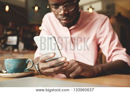 Film Effect. Handsome African Student In Shirt And Glasses Using Mobile Phone, Looking At The Screen