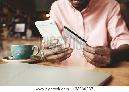 African American Man In Casual Shirt Paying With Credit Card Online While Making Orders Via The Inte