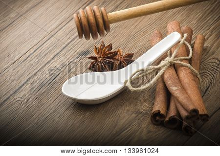 wooden honey dipper and spices on wood table
