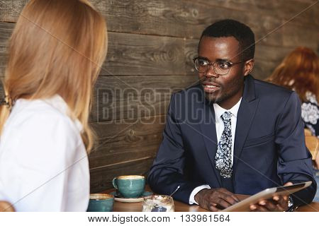 Young African Businessman Holding Tablet And Sharing Data With Female Caucasian Colleague During Cof