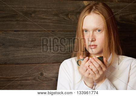 Young Caucasian Girl Holding A Cup Of Tasty Coffee With Both Hand In A Café. Blond Blue-eyed Wo