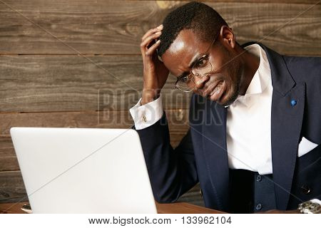 Dark-skinned Businessman In Formal Suit And Glasses Having Stress While Working On Laptop At The Caf