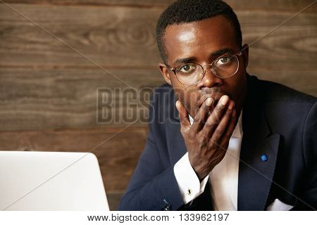 Did I Say Something Wrong? Shocked Young Afro-american Man In Formal Wear And Glasses Covering Mouth