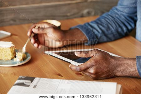 Close Up Shot Of Dark-skinned Man's Hands Holding A Spoon In One Hand And Blank Copy Space Tablet In