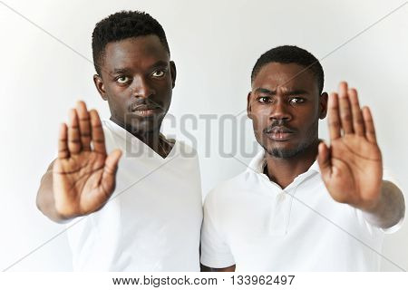 Portrait Of Two African Friends Showing Stop Gesture With Their Open Palms, Saying 'stop Talking' Or