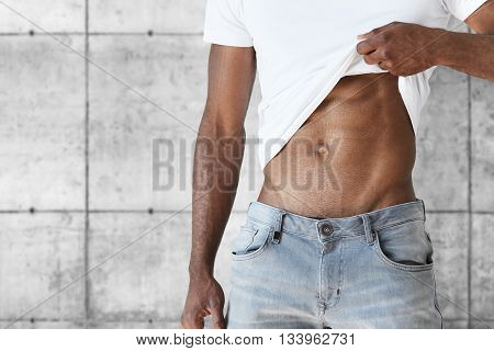 Cropped Shot Of Young African Sportsman, Undressing, Demonstrating His Tense Abs. Muscular Toned Fit