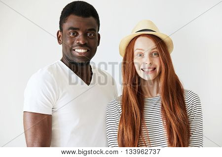 Full Face Portrait Of Young Couple Deliberately Smiling At Camera In White Studio. Red-head Girl Wit