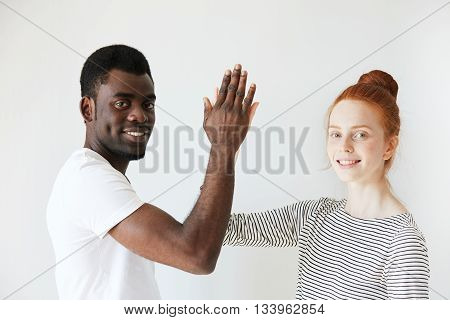 Portrait Of A Young Couple Making High Five And Smiling At Camera In White Studio. Mix Of African Am