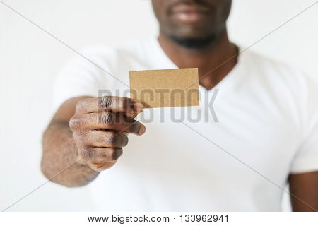 African American Man Holding A Brown Empty Business Card With Outstretched Arm. He Showing This Blan