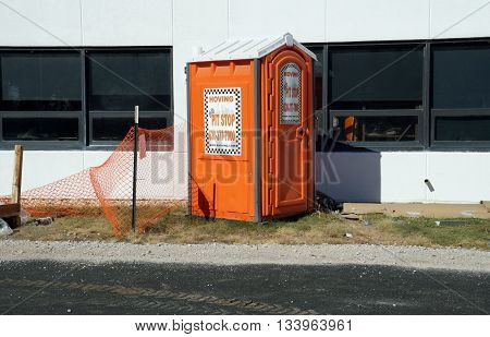 JOLIET, ILLINOIS / UNITED STATES - OCTOBER 25, 2015: A portable toilet stands outside Joliet Junior College.