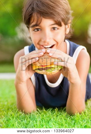 Portrait of a cute happy teen boy lying down on fresh green grass and with pleasure eating burger, tasty, but unhealthy food
