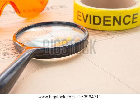 magnifying glass with forensic tool for crime scene investigation