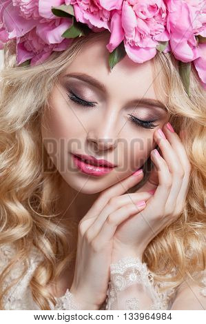 Portrait of cute young girl with beautiful makeup . Blond hair wavy curls on her head a crown of pink peonies . Beauty clean skin . Photographed in studio on a white background. Light Tone .