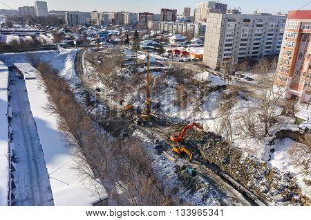 Tyumen, Russia - February 15, 2016: Aerial view onto construction works on strengthening of Tyumenka river bank near Polevaya Street