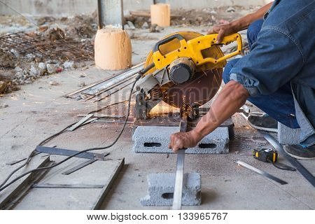 spark from worker cutting metal by hacksaw at construction site
