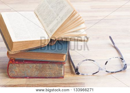 Antiques books stack with open one and glasses, copy space on wooden table desktop