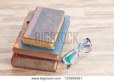 Antique books stack and glasses on wooden table desktop