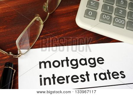 Paper with words mortgage interest rates on a wooden background.