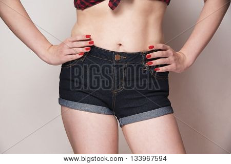 retro style dressed woman wearing jeans with her hands on hips