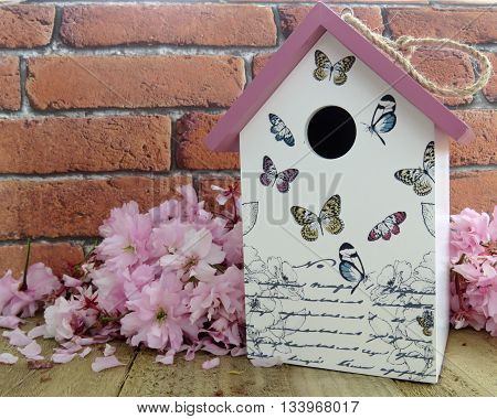 Decorative birdhouse with pink blossom on a wooden surface