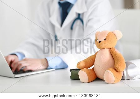Pediatrician doctor with teddy bear and laptop in office