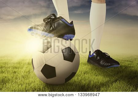 Close up of foot of football player and a ball ready to start a game on the meadow