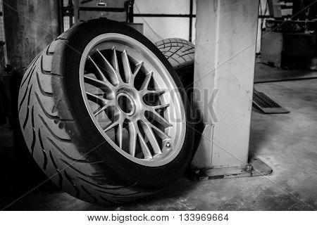 Sport wheel and tyre between maintenance hour in garage gray scale