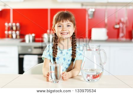 Cute little girl with jug of water in kitchen