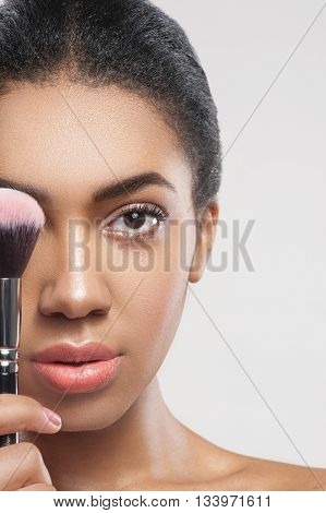 Portrait of beautiful african girl holding a brush with blush near her eye. She is standing and looking forward with confidence. Isolated