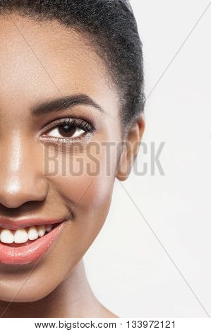 Close up of half of female face with beautiful skin. Pretty african girl is looking forward and smiling. Isolated