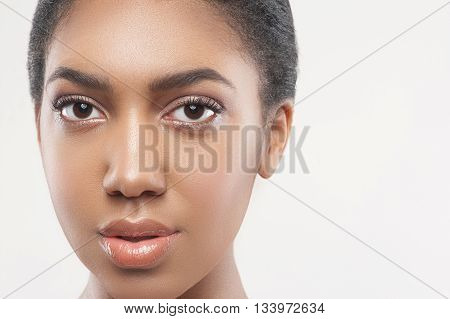 Portrait of pretty young mulatto girl caring of her skin. She is looking at camera with confidence. Isolated and copy space in right side