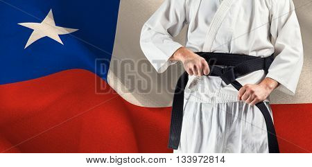 Mid section of fighter tightening karate belt against digitally generated chile national flag