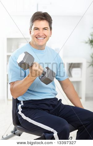 Smiling strong fitness man working out at home